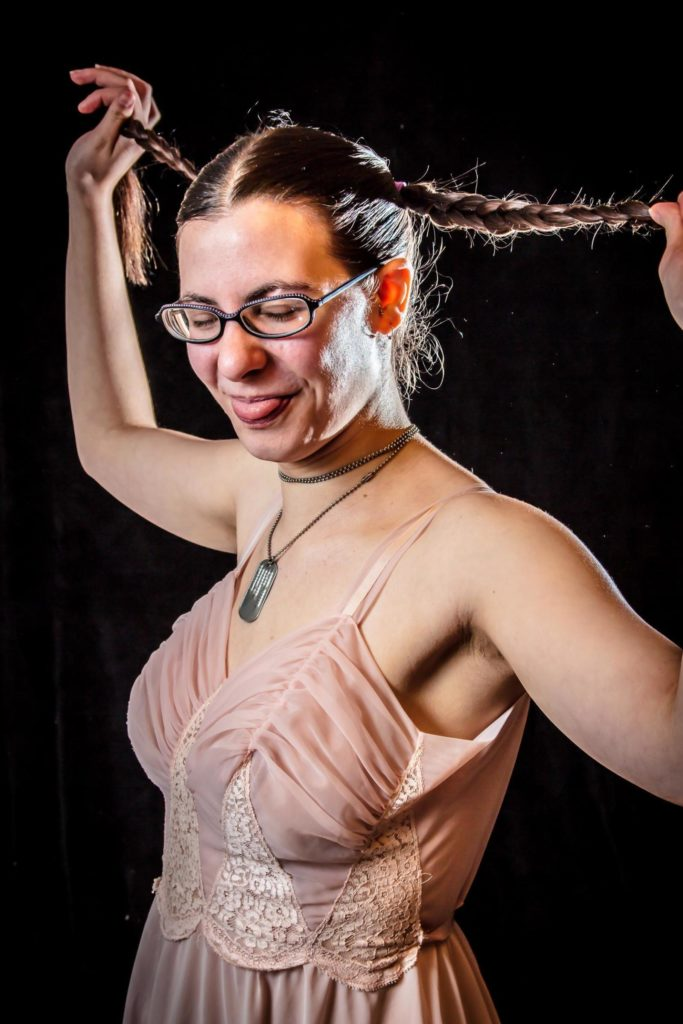 portrait of young brown haired woman in braided pig tails wearing glasses beige dress sticking out tongue army dog tags copyright adrian feliciano photography photographer boston massachusetts alphajulietfoxtrot.com