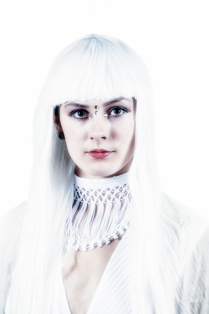 bright high key white portrait of woman in white wig wearing white fringed collar and white tunic in front of white background copyright adrian feliciano alphajulietfoxtrot.com